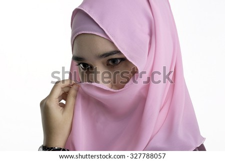 Fashion portrait of young beautiful muslim woman cover her mouth with pink color hijab isolated on white background - stock photo