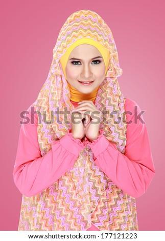 Fashion portrait of young beautiful muslim woman with pink costume wearing hijab - stock photo