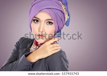 Fashion portrait of young beautiful muslim woman with purple costume wearing hijab - stock photo