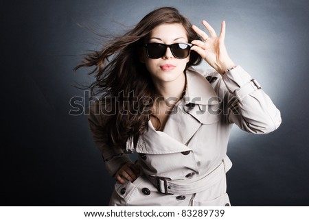 Fashion portrait of young beautiful woman in the raincoat and sunglasses - stock photo