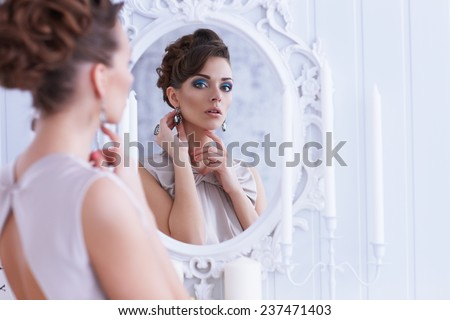 Fashion portrait of young beautiful woman looking in antique mirror, bright makeup and jewelery - stock photo