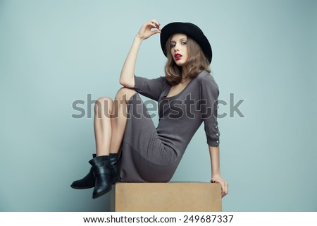 Fashion portrait of young beautiful woman model  in casual wear. Black boots, hat and grey dress. Copy space. - stock photo