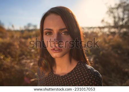 Fashion portrait of young beautiful woman. On autumnal sunset field background. - stock photo