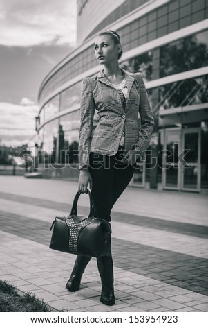 Fashion portrait of young brunette in full length on street. Black and white - stock photo