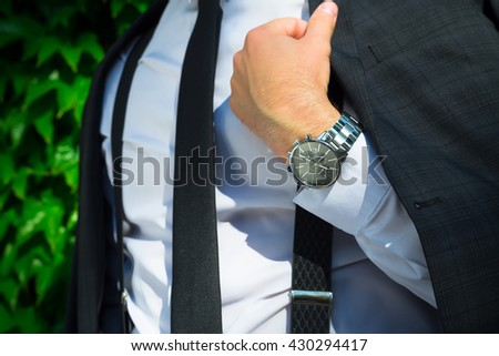 Fashion portrait of young businessman handsome model man in casual cloth suit with accessories on hands.Men accessories.Confident sharp dressed man in luxury suit - stock photo