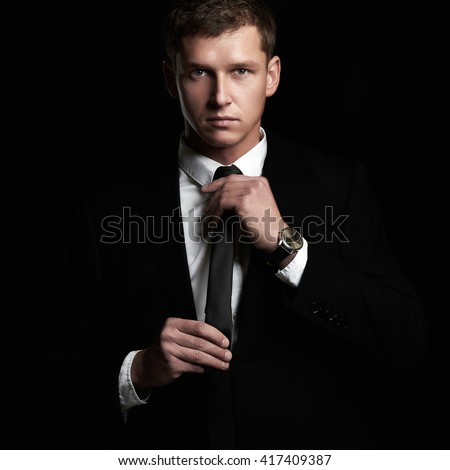 fashion portrait of young Businessman standing on black background. handsome Man in suit and tie - stock photo