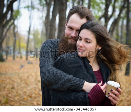Fashion portrait of young couple drinking coffee in autumn park outdoor, image toned and noise added. Hipster man with beard and moustache embracing his beautiful girlfriend outside. - stock photo