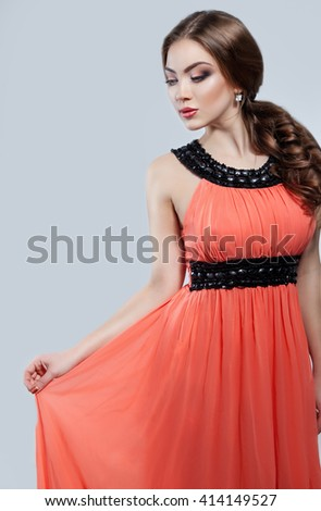 Fashion portrait of young elegant woman in evening coral dress and curly long hair. Studio shoot. - stock photo