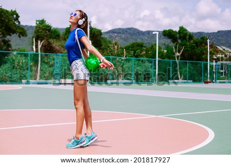 Fashion portrait of young fit sportive woman posing outdoor  in summer got sunny day, wearing bright neon sport clothes back back and sunglasses. - stock photo