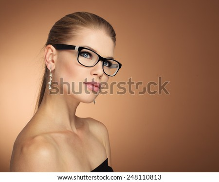 Fashion portrait of young glamour female in optical eyewear with black frame over golden background. Pretty girl with beautiful evening makeup wearing jewelery posing in studio.  - stock photo