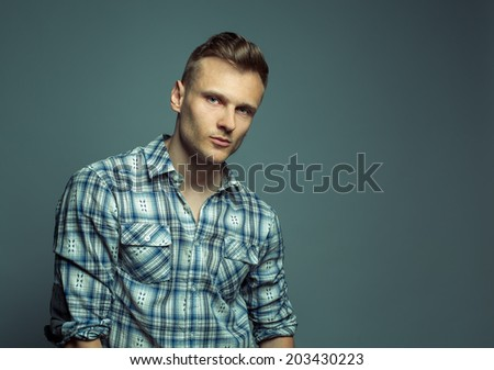 Fashion portrait of young handsome blond man in shirt poses over grey background - stock photo