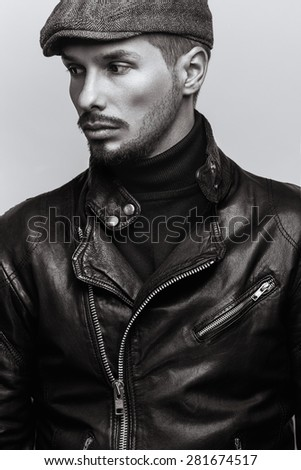 Fashion portrait of young handsome brutal bearded man in leather jacket and in cap. - stock photo
