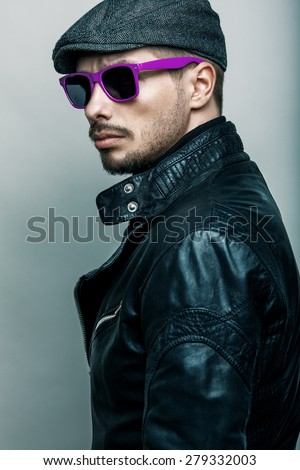 Fashion portrait of young handsome brutal bearded man in leather jacket and sunglasses. - stock photo
