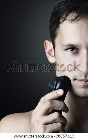 Fashion portrait of Young handsome man. male chin and electric shaver - stock photo