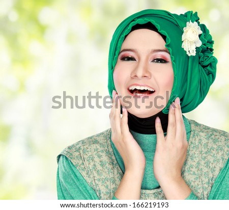 Fashion portrait of young happy beautiful muslim woman with green costume wearing hijab - stock photo