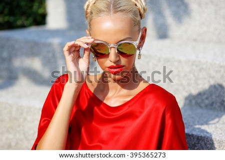 Fashion portrait of young pretty blonde girl in red dress and sunglasses. Beautiful woman model posing outdoor - stock photo