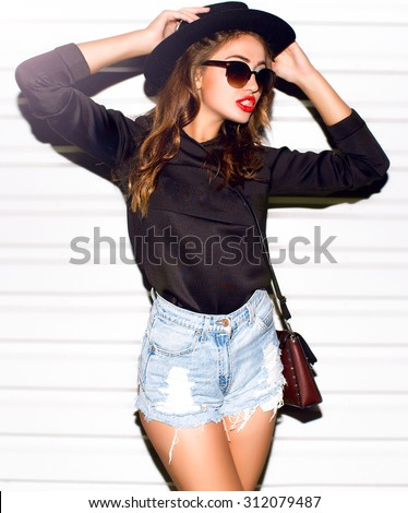 Fashion portrait of young pretty hipster woman with blonde hairs and big full bright lips wearing stylish black outfit,denim swag shorts hat glasses and t shirt with funny print.urban wall background - stock photo