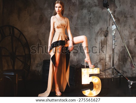Fashion portrait of young sensual Blonde woman with long hair and hairstyle,natural make up.Studio beauty portrait.Rich and long dress,Elegant women's heels, perfect legs expensive elegant gold dress - stock photo