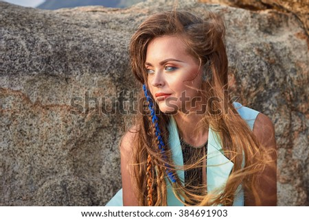 Fashion portrait of young  sexy beautiful girl, model, woman in blue stylish clothes and braids near mountain in summer, boho style vacation photography - stock photo