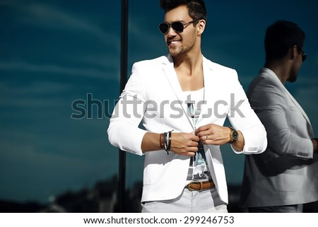 Fashion portrait of young sexy businessman handsome  model man in casual cloth suit in sunglasses in the street - stock photo