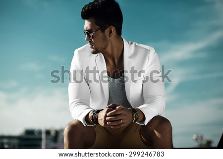 Fashion portrait of young sexy businessman handsome  model man in casual cloth suit in sunglasses sitting  in the street behind blue sky - stock photo