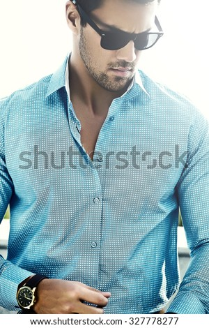 Fashion portrait of young sexy handsome model man in casual cloth in sunglasses in the street - stock photo
