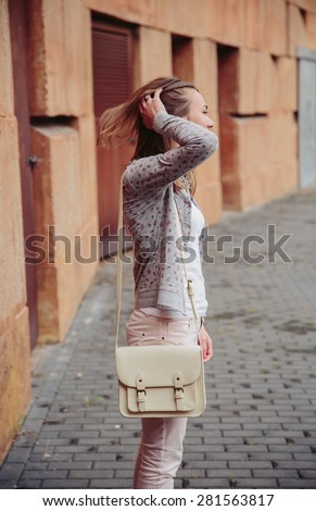 Fashion portrait of young trendy woman wearing gray jacket, pink jeans and white satchel bag over touching her hair outdoors - stock photo