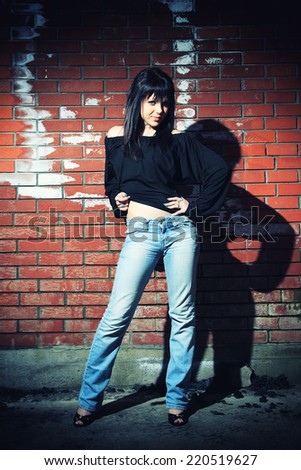 fashion portrait of young woman with a brick wall in the background - stock photo