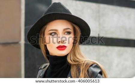 Fashion portrait stylish pretty woman outdoor. Young woman wearing a rock black style having fun in city. Street fashion. Red lipstick. Black hat. - stock photo