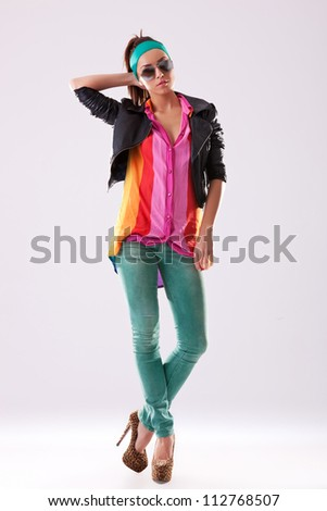 fashion pose of a sexy young woman in leather jacket jeans and high heels - stock photo