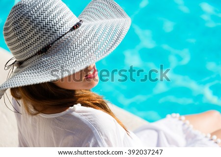 Fashion Pretty woman on summer vacation relaxing at luxury hotel resort spa poolside. Young  fashionable lady wearing sun hat and white kaftan. - stock photo