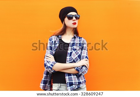 Fashion pretty woman wearing a black hat, sunglasses and checkered shirt over colorful background - stock photo