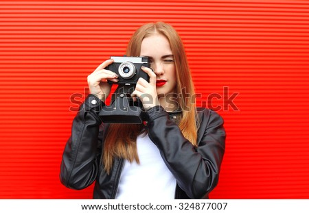 Fashion pretty woman with old retro camera over red background - stock photo