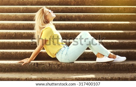 Fashion pretty young woman relaxing and enjoys sunny summer day in the city - stock photo
