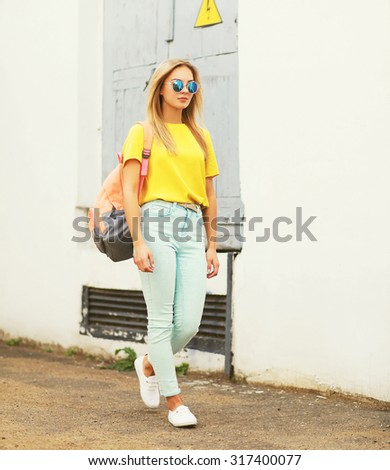 Fashion pretty young woman wearing a sunglasses and t-shirt with backpack walking in the city - stock photo