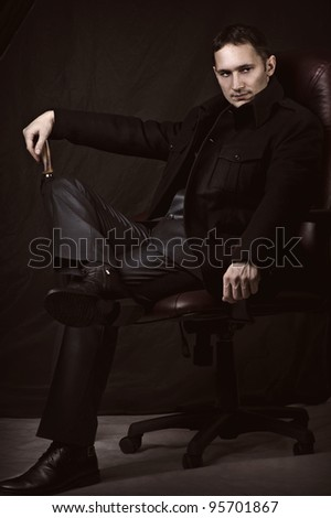 Fashion retro portrait of handsome fashionable man in coat and suit - stock photo
