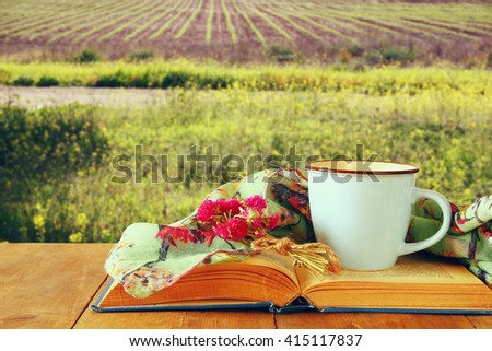 fashion scarf with cup of coffee and old book on a wooden table in front of summer field landscape. vintage filtered  - stock photo