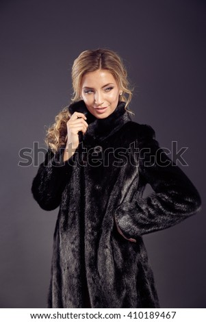 Fashion seductive blond hair lady in an elegant fur coat and black underwear on a dark background. Retouched. - stock photo