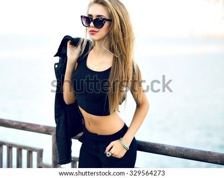Fashion sensual glamour sexy blonde woman, posing near sea, cold windy autumn weather, black trendy clothes and sunglasses, toned film vintage colors. - stock photo
