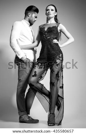 fashion sexy couple dressed elegant posing in the studio - bw - stock photo