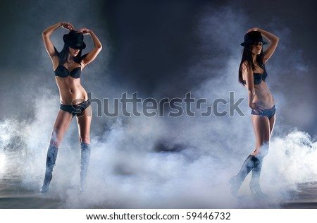 Fashion shoot of young and sexy woman in erotic lingerie over dark background - stock photo