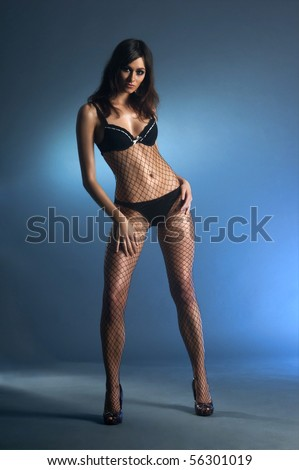 Fashion shoot of young sexy lady over smoke and darkness - stock photo