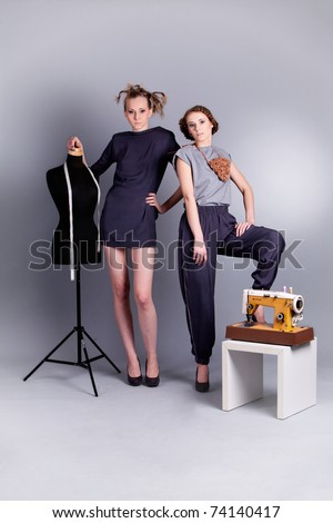 Fashion shoot: two young, sensual women in fashionable clothes with sewing mannequin and sewing machine on grey background - stock photo