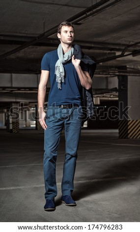 Fashion shot: a handsome young man in underground parking  - stock photo