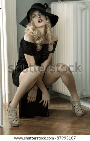 fashion shot of a beautiful and sensual young lady posing wearing a huge hat and an elegant black dress - stock photo
