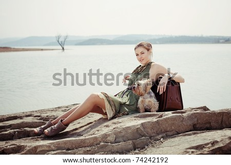 Fashion shot of a beautiful girl on the lake with a suitcase and a dog (Yorkshire terrier) - stock photo