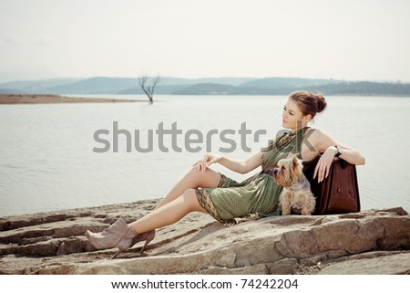 Fashion shot of a beautiful, professional model on the lake with a suitcase and a dog (Yorkshire terrier) - stock photo