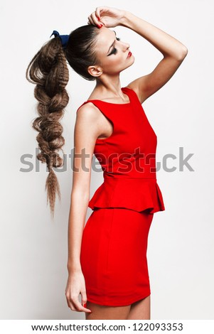 Fashion shot of a beautiful professional model, posing in a red dress in the studio. - stock photo