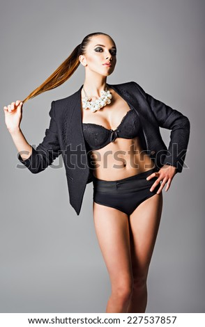 Fashion shot of a beautiful young girl wearing black jacket, bra and pearl necklace  - stock photo