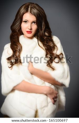 Fashion shot of a beautiful young woman in white fur coat. - stock photo